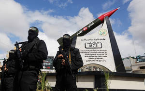 Photo - Hamas military wing members take part in a ceremony to inaugurate a monument marking the anniversary of the death of  a senior Hamas official Ibrahim Maqadama, killed in an Israeli air strike in 2003, in Gaza City , Monday, March 10, 2014. The monument represents a model of the Hamas made longer-range M75 missile which has  a range of about 80 kilometers and was used for the first time in 2012 against targets in Israel. (AP Photo/Hatem Moussa)