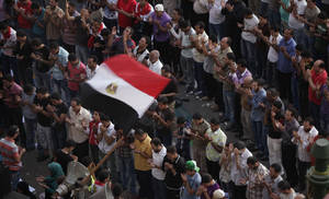 Photo -   Egyptian protesters perform prayers in front of a national flag, during a protest at Tahrir Square, Cairo, Egypt, Friday, June 8, 2012. Hundreds gathered in Cairo's Tahrir Square, the focal point of Egyptian uprising, to demonstrate against presidential candidate Ahmed Shafiq, Hosni Mubarak's last prime minister, ahead of a run-off vote. (AP Photo/Amr Nabil)