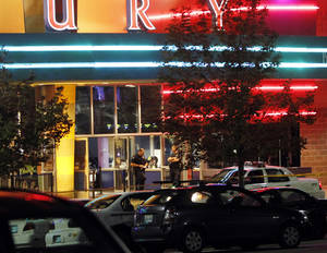 Photo -   Police are pictured outside of a Century 16 movie theatre where as many as 14 people were killed and many injured at a shooting during the showing of a movie at the in Aurora, Colo., Friday, July 20, 2012. (AP Photo/Ed Andrieski)