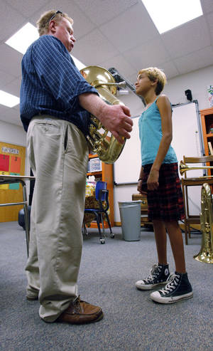 Photo - Left: Roger Nunn, band coordinator, works with McKalya Rodriquez from Longfellow Middle School as students try out band instruments.