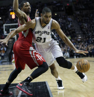 Photo - San Antonio Spurs' Tim Duncan (21) works the ball around Houston Rockets' Marcus Morris, left, during the first quarter of an NBA basketball game on Friday, Dec. 28, 2012, in San Antonio. (AP Photo/Eric Gay)
