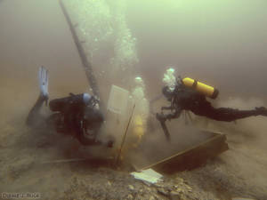 Photo - In this photo taken June 16, 2013, divers inspect a hole being dug beside a wooden beam jutting from the floor of Lake Michigan that an exploration group believes may have been part of the 17th century ship the Griffin. (AP Photo/Great Lakes Exploration Group, David J. Ruck)