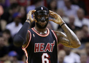 Photo - Miami Heat small forward LeBron James (6) adjusts his mask during the first half of an NBA basketball game against the New York Knicks in Miami, Thursday, Feb. 27, 2014. (AP Photo/Alan Diaz)