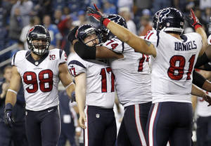 Photo -   Houston Texans kicker Shayne Graham (17) is mobbed by teammates Wade Smith (74) and Owen Daniels (81) after kicking the game-winning field goal in overtime of an NFL football game against the Detroit Lions at Ford Field in Detroit, Thursday, Nov. 22, 2012. Looking on at left is Connor Barwin. The Texans won 34-31. (AP Photo/Rick Osentoski)