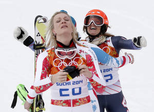 Photo - Germany's Maria Hoefl-Riesch, foreground, and United States' Julia Mancuso react to their gold and bronze medal finishes in the women's supercombined at the Sochi 2014 Winter Olympics, Monday, Feb. 10, 2014, in Krasnaya Polyana, Russia. (AP Photo/Christophe Ena)