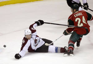 Photo - Minnesota Wild's Matt Cooke shoots a puck past Colorado Avalanche's Erik Johnson, which goalie Semyon Varlamov stopped in the first period of an NHL hockey game, Saturday, Jan. 11, 2014, in St. Paul, Minn. (AP Photo/Jim Mone)