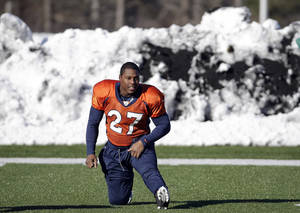 Photo - Denver Broncos running back Knowshon Moreno (27) stretches in front of a pile of snow during practice Wednesday, Jan. 29, 2014, in Florham Park, N.J. The Broncos are scheduled to play the Seattle Seahawks in the NFL Super Bowl XLVIII football game Sunday, Feb. 2, in East Rutherford, N.J. (AP Photo/Mark Humphrey)