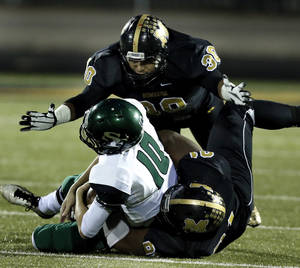 Photo - Midwest City's Brandon Jones, below, and Cameron Carson bring down quarterback  Keaton Torre in high school football action as the Midwest City Bombers play the Edmond Santa Fe Wolves on Friday, Nov. 15, 2013  in Midwest City, Okla. Photo by Steve Sisney, The Oklahoman
