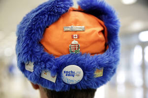 Photo - A skating fan sports a cap with Olympic pins on it prior to the start of the women's 500-meter speedskating race at the Adler Arena Skating Center at the 2014 Winter Olympics, Tuesday, Feb. 11, 2014, in Sochi, Russia. (AP Photo/Matt Dunham)