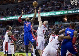 Photo - Detroit Pistons' Greg Monroe (10) shoots while Washington Wizards' Marcin Gortat (4), of Poland, defends during the during the first half of an NBA basketball game in Washington, Saturday, Dec. 28, 2013. Wizards' Bradley Beal (3) and Trevor Ariza (1) and Pistons' Josh Smith (6) look on. (AP Photo/Manuel Balce Ceneta)