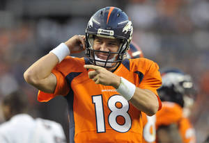 Photo -   Denver Broncos quarterback Peyton Manning reacts after his team scored a touchdown in the first half of an NFL football preseason game against the Seattle Seahawks, Saturday, Aug. 18, 2012, in Denver. (AP Photo/Jack Dempsey)