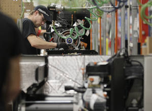 photo - In this Nov. 16, 2012 photo, an employee works on assembly line at Generac Power Systems, Inc., in Whitewater, Wis. After U.S. manufacturing shrunk in November, it grew slowly in December and hiring increased, a sign of modest economic momentum heading into the new year. (AP Photo/Nam Y. Huh)