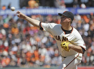 Photo - San Francisco Giants starting pitcher Matt Cain throws to the Colorado Rockies during the first inning of a baseball game on Saturday, April 12, 2014, in San Francisco. (AP Photo/Marcio Jose Sanchez)