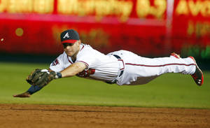 Photo - Atlanta Braves second baseman Tommy La Stella (7) makes a diving catch on a ball hit by New York Mets' Daniel Murphy  in the eighth inning of a baseball game in Atlanta, Wednesday, July 2, 2014.  La Stella flipped the ball to second base in time to retire the base runner.  (AP Photo/John Bazemore)