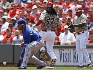Photo - Cincinnati Reds' Johnny Cueto (47) is safe at first on a bunt-single as Toronto Blue Jays first baseman Edwin Encarnacion, left, catches the throw from starting pitcher R.A. Dickey in the fifth inning of a baseball game on Sunday, June 22, 2014, in Cincinnati. (AP Photo/Al Behrman)