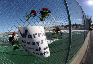 Photo - Roses and a sign of support are woven into a cyclone fence around a tennis court at Arapahoe High School in Centennial, Colo., on Saturday, Dec. 14, 2013. The school was the scene of a shooting on Friday that left a student gunman dead and two other students injured. (AP Photo/David Zalubowski)