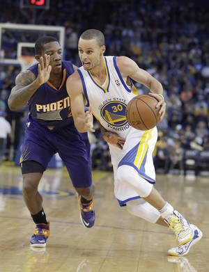 Photo - Golden State Warriors guard Stephen Curry (30) drives past against Phoenix Suns guard Eric Bledsoe (2) during the second half of an NBA basketball game in Oakland, Calif., Friday, Dec. 27, 2013. Warriors won 115-86. (AP Photo/Tony Avelar)