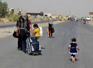 Photo - In this Sunday, June 29, 2014 photo, an Iraqi family leave their hometown Mosul, walking towards Irbil, on the outskirts of the northern city of Mosul, Iraq. The al-Qaida breakaway group that has seized much of Syria and Iraq has formally declared the establishment of a new Islamic state, demanding allegiance from Muslims worldwide in a move that could further strain relations with other militant groups. (AP Photo)