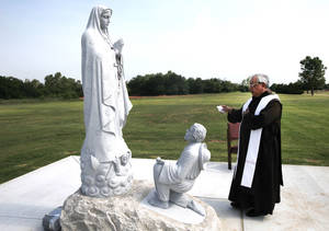 Photo - The Rev. Raul Reyes, pastor of Little Flower Catholic Church, blesses the Our Lady of Guadalupe statue and new garden Monday at Sunny Lane Cemetery, 3900 SE 29 in Del City. <strong>Steve Gooch - The Oklahoman</strong>