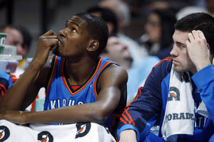 Photo - Oklahoma City Thunder forwards Kevin Durant, left, and Nick Collison check the scoreboard as they Thunder fall behind by 40 points in the fourth quarter of the Denver Nuggets' 119-90 victory over the Thunder in an NBA basketball game in Denver on Wednesday, March 3, 2010. (AP Photo/David Zalubowski)