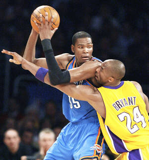 photo - Lakers guard Kobe Bryant, right, defends Thunder forward Kevin Durant during Los Angeles' 95-92 win Tuesday. AP PHOTO