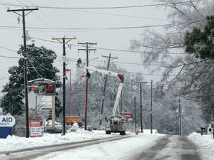Photo - A power crew works to repair lines off highway 176 Thursday, Feb. 13, 2014, in Chapin, S.C. At the peak of the winter storm 350 thousand costumers were without power.  Now that the snow and ice have ended in South Carolina, hundreds of thousands of residents are waiting for power to return so life can get back to normal.  (AP Photo/Mary Ann Chastain)