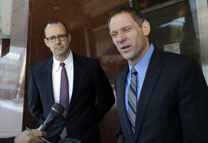 Photo - Prosecutor Andrew Winter, left, listens as fellow prosecutor Steve Schleicher talks to reporters after a federal jury Tuesday, March 19, 2013, in Minneapolis convicted three alleged members of an American Indian gang accused of terrorizing people in the Upper Midwest. (AP Photo/Jim Mone)