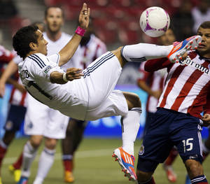 Photo -   Vancouver Whitecaps' Camilo Sanvezzo, left, of Brazil, attempts a bicycle kick on goal as Chivas USA's Alejandro Moreno, of Venezuela, looks on during the first half of an MLS soccer match, Wednesday, Oct. 3, 2012, in Vancouver, British Columbia. (AP Photo/The Canadian Press, Darryl Dyck)