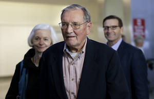Photo - Merrill Newman, center, walks beside his wife Lee, left, and his son Jeffrey after arriving at San Francisco International Airport on Saturday, Dec. 7, 2013. Newman was detained in North Korea late October at the end of a 10-day trip to North Korea, a visit that came six decades after he oversaw a group of South Korean wartime guerrillas during the 1950-53 war. He was released from North Korea early Saturday. (AP Photo/Ben Margot)