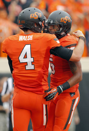 Photo - Oklahoma State's J.W. Walsh, left, and Josh Stewart celebrate after Walsh threw Stewart a touchdown pass during Saturday's game vs. Louisiana-Lafayette. Walsh and Stewart were high school teammates at Denton (Texas) Guyer.  PHOTO BY SARAH PHIPPS, The Oklahoman