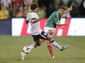 Photo - Mexico's Hector Moreno, right, shoots the ball past the United States' Jermaine Jones during the first half of a World Cup qualifying soccer match Tuesday, Sept. 10, 2013, in Columbus, Ohio. (AP Photo/Jay LaPrete)