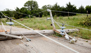 Photo - A power line lies across a road Wednesday near the Lake Stanley Draper water treatment plant in Oklahoma City. Photo by Sarah Phipps, The Oklahoman