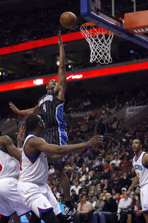 Photo - Orlando Magic's Arron Affialo (4) shoot against the Philadelphia 76ers in the first half of an NBA basketball game, Tuesday, Feb. 26, 2013, in Philadelphia. (AP Photo/H. Rumph Jr)
