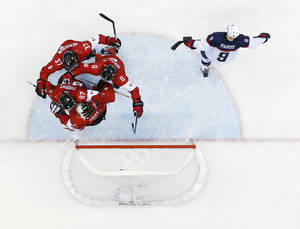 Photo - USA forward Zach Parise skates off the ice as Canadian players celebrate after a men's semifinal ice hockey game at the 2014 Winter Olympics, Friday, Feb. 21, 2014, in Sochi, Russia. Canada won 1-0 to advance to the gold medal game. (AP Photo/David J. Phillip)