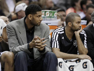 Photo - San Antonio Spurs'  Tim Duncan, left, who did not play, and Tony Parker, right, of France, sit on the bench during the first half of an NBA basketball game against the Los Angeles Lakers, Wednesday, April 16, 2014, in San Antonio. Los Angeles won 113-100. (AP Photo/Eric Gay)