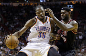 Photo - Oklahoma City Thunder small forward Kevin Durant withstands pressure from Miami Heat small forward LeBron James during the fourth period of the Jan. 29 NBA basketball game between the Thunder and Heat. The Thunder won the game 112-95.  <strong>Alan Diaz - AP</strong>