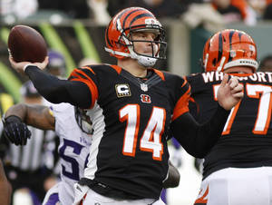 Photo - Cincinnati Bengals quarterback Andy Dalton (14) passes against the Minnesota Vikings in the second half of an NFL football game, Sunday, Dec. 22, 2013, in Cincinnati. Dalton threw four touchdown passes as Cincinnati won 42-14. (AP Photo/David Kohl)