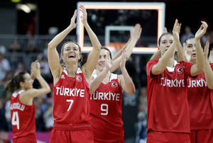 Photo -   Turkey's Nilay Kartaltepe (7) and Esmeral Tuncluer (9) celebrate with tammates after their win over the Czech Republic in a preliminary women's basketball game at the 2012 Summer Olympics, Monday, July 30, 2012, in London. (AP Photo/Eric Gay)