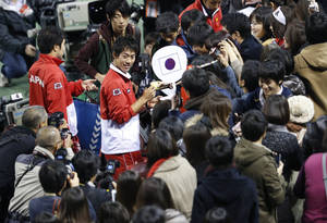 Photo - Kei Nishikori, center, of Japan signs autographs for fans after Japan's win over Canada at the 1st round of Davis Cup World Group tennis in Tokyo, Sunday, Feb. 2, 2014. (AP Photo/Shizuo Kambayashi)