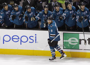 Photo - San Jose Sharks' Joe Pavelski gets congratulations from the bench after scoring during the shootout against the Anaheim Ducks in an NHL hockey game, Saturday, Nov. 30, 2013, in San Jose, Calif. The Sharks won 4-3. (AP Photo/George Nikitin)