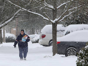 Photo - Postal employee Lisa Calloway trudges through the snow as she delivers mail in Eugene, Ore. on Friday, Feb. 7, 2014.  Snowfall starting late in the morning Friday will be widespread, dropping a foot or more in mountainous parts of Southern Oregon and 2 to 8 inches in Western Oregon valleys that got slammed Thursday, the National Weather Service said. (AP Photo/The Register-Guard, Brian Davies)