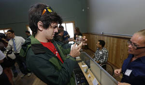 "Photo - Sam Pyle, left, inspects a ""sniff jar"" containing a sample of recreational marijuana at Top Shelf Cannabis, Tuesday, July 8, 2014, in Bellingham, Wash., on the first day of legal sales in the state.  (AP Photo/Ted S. Warren)"