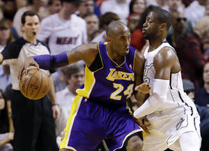 photo - Los Angeles Lakers guard Kobe Bryant (24) drives against Miami Heat guard Dwyane Wade during the first half of an NBA basketball game, Sunday, Feb. 10, 2013, in Miami. (AP Photo/Wilfredo Lee)