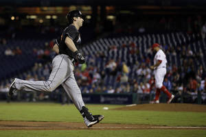 Photo - Miami Marlins' Ed Lucas, left, rounds the bases after hitting a home run off Philadelphia Phillies relief pitcher Cesar Jimenez during the 10th inning of a baseball game on Wednesday, Sept. 18, 2013, in Philadelphia. Miami won 4-3 in 10 innings. (AP Photo/Matt Slocum)