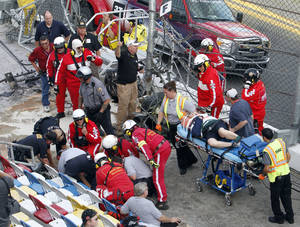 photo - Injured spectators are treated after a crash at the conclusion of the NASCAR Nationwide Series auto race Saturday, Feb. 23, 2013, at Daytona International Speedway in Daytona Beach, Fla. Driver Kyle Larson's car hit the safety fence sending car parts and other debris flying into the stands. (AP Photo/David Graham)