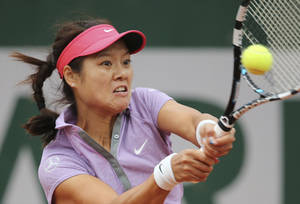 Photo - Chinas Li Na returns the ball to France's Kristina Mladenovic during their first round match of  the French Open tennis tournament at the Roland Garros stadium, in Paris, France, Tuesday, May 27, 2014. (AP Photo/David Vincent)