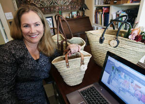 Photo -      Laura Benson, who owns Jeanne Beatrice, a company that sells handmade baskets, poses with some of her basket creations in her home-based business in Edina, Minn.  AP Photo  <strong>Jim Mone -  AP </strong>
