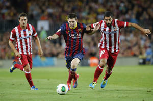 Photo - Barcelona's Lionel Messi from Argentina in action with Atletico de Madrid's Arda Turan, right, and Koke Resurreccion, left, during a Spain Super Cup soccer match at the Camp nou stadium in Barcelona, Spain, Wednesday, Aug. 28, 2013. (AP Photo/Emilio Morenatti)