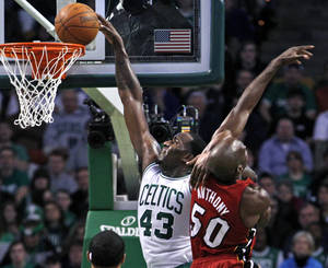 photo - Boston Celtics center Kendrick Perkins (43) scores over Miami Heat center Joel Anthony (50) during the first half of an NBA basketball game in Boston, Sunday, Feb. 13, 2011. (AP Photo/Elise Amendola)
