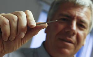 Photo - Garry Harvey, the official engraver of the Royal and Ancient Golf Club, holds up an engraving tool during the British Open Golf Championship at Muirfield, Scotland, Saturday July 20, 2013. (AP Photo/Alastair Grant)